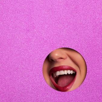 Lábios vermelhos brilhantes através do fundo de papel violeta shimmer.