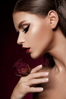 Lábios vermelhos e olhos esfumaçados compõem. retrato de senhora glamour.