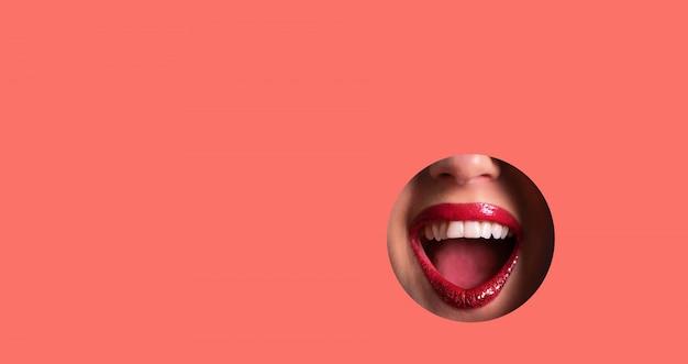 Lábios vermelhos e sorriso brilhante através do buraco no fundo de papel coral vivo