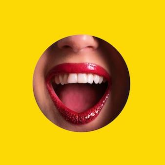 Lábios vermelhos, sorriso brilhante através do buraco no fundo de papel amarelo. compõem o conceito de artista