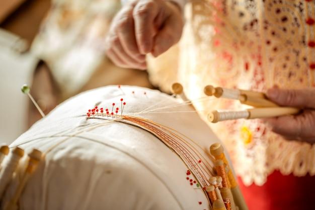 Lace tecelagem em bobinas é um velho artesanato popular russo. as mãos rendas anexado agulhas para tecer o padrão de renda.