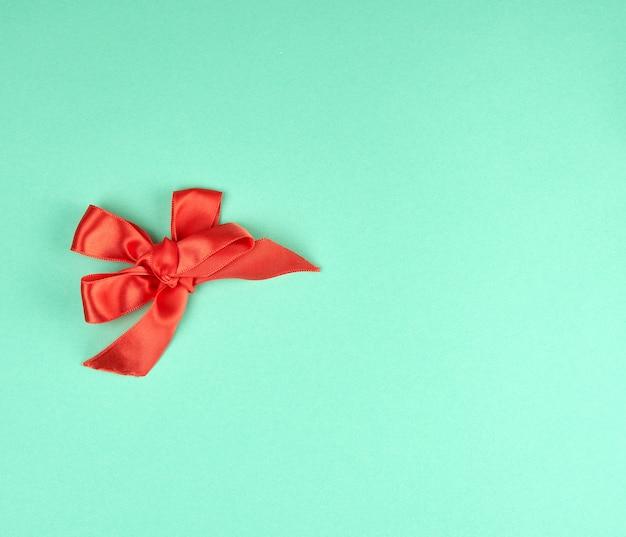 Laço atado de fita de seda vermelha sobre um fundo verde