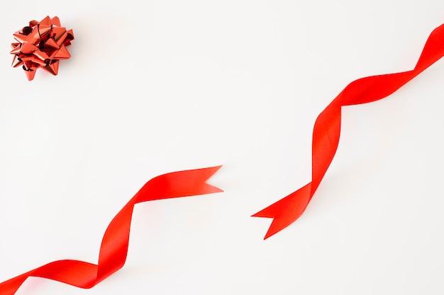 Laço de cetim vermelho e fitas em fundo branco