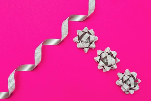 Laço de fita de papel prata sobre fundo rosa