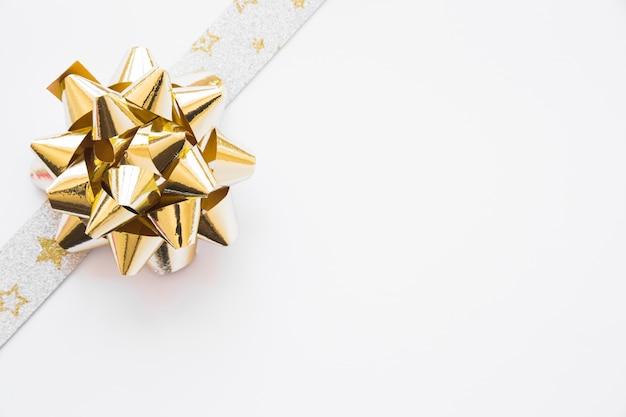 Laço de fita de prata dourada decorado em fundo branco