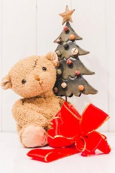 Laço de fita vermelha com ursinho de pelúcia e árvore de natal