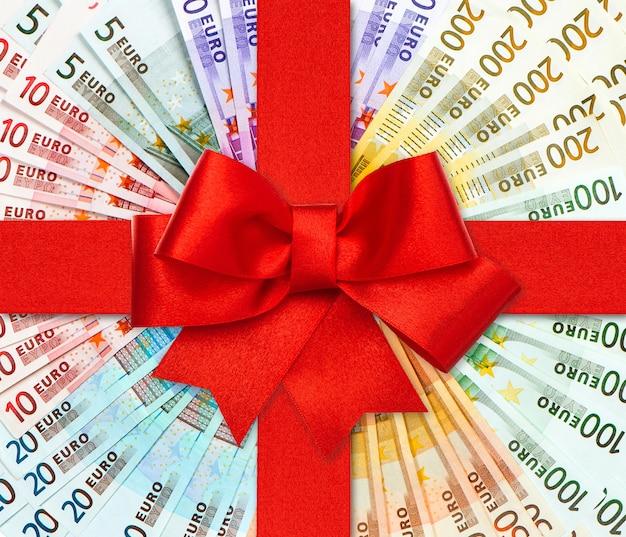 Laço de fita vermelha de presente sobre as notas de euro. moeda europeia. fundo de dinheiro. conceito de cartão-presente de compras