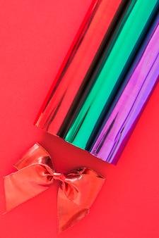 Laço de fita vermelha e glitter enrolado em papel em fundo vermelho