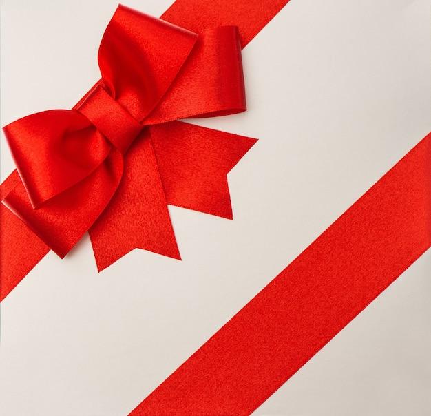 Laço de fita vermelha na caixa de presente cinza. fundo de feriados