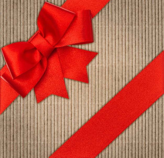 Laço de fita vermelha sobre papelão reciclado da natureza. fundo de feriados