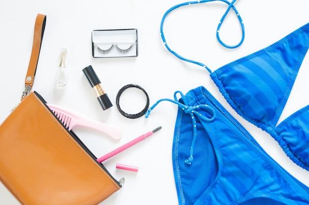 Laço plano da moda do verão com biquíni azul e acessórios para meninas no fundo branco