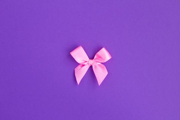Laço rosa no centro da mesa violeta. vista do topo. copie o espaço. mesa de férias.