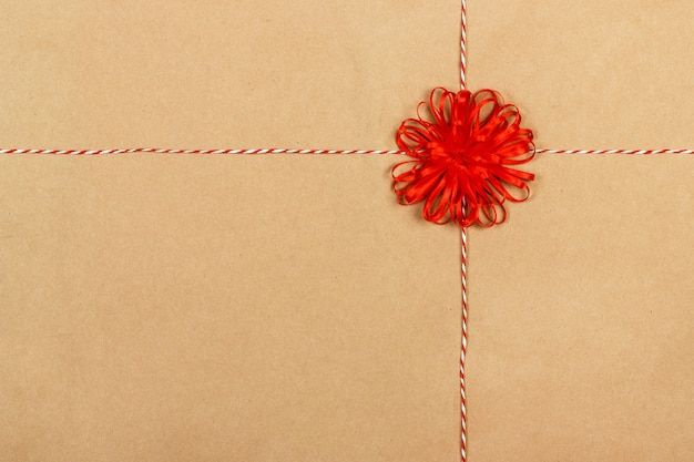 Laço vermelho de presente com fitas em fundo de papel ofício