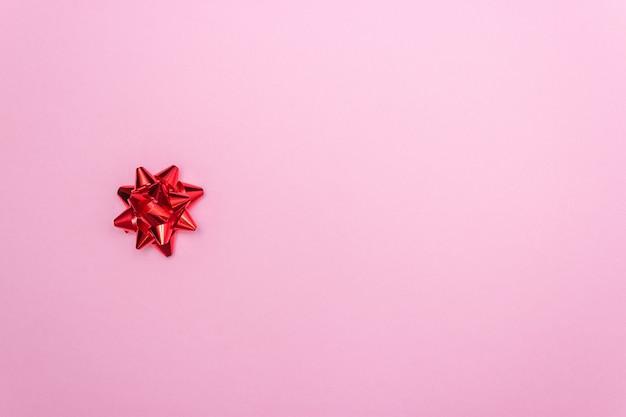 Laço vermelho de presente em um fundo rosa