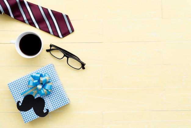 Laço, vidros, bigode, caixa de presente e copo de café vermelhos no fundo de madeira amarelo da tabela.