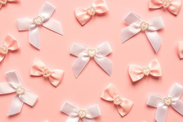 Laços de cetim rosa com padrão de corações de pérola na superfície rosa.