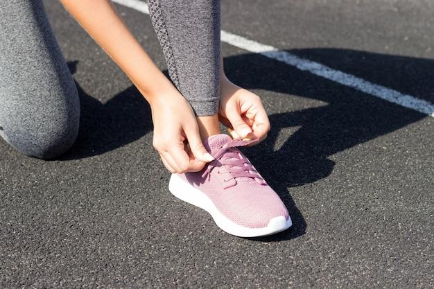 Laços de menina em seu tênis rosa para correr. sem rosto closeup. conceito ao ar livre, luz solar, estádio, esporte e fitness