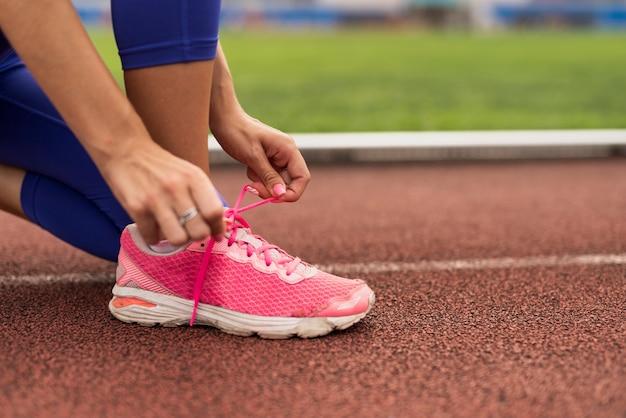 Laços de sapatos de vincular mulher close-up