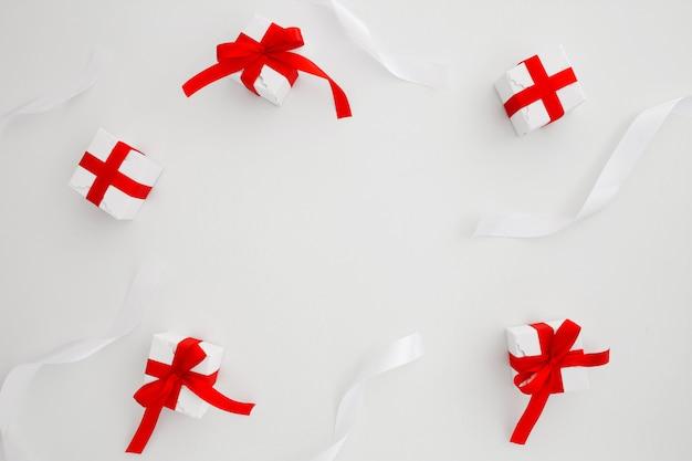 Laços e presentes de natal em fundo branco com copyspace no meio