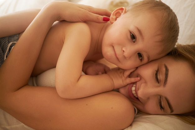 Laços familiares e conceito de maternidade. imagem recortada da bela jovem mãe europeia relaxando no quarto, deitada em lençóis brancos com seu adorável filho bebê, segurando-o com força e sorrindo alegremente