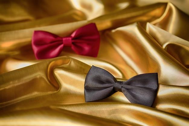 Laços vermelhos e pretos em fundo de tecido dourado