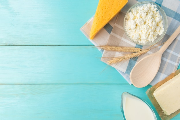 Lacticínios. leite, kefir, queijo cottage, queijo e soro de leite na mesa de madeira azul.