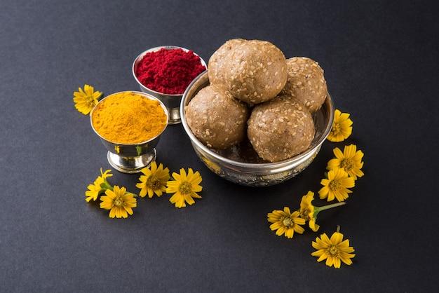 Laddu de gergelim ou tilgul com haldi kumkum com flores para o festival makar sankranti, foco seletivo