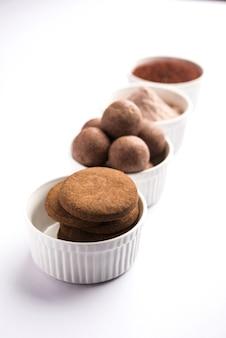 Laddu nachni ou ragi e biscoitos ou cookies feitos com milho, açúcar e ghee. é um alimento saudável da índia. servido em uma tigela ou prato com todo cru e pó
