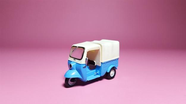 Lado da frente do veículo tuk-tuk ou azul sobre fundo rosa