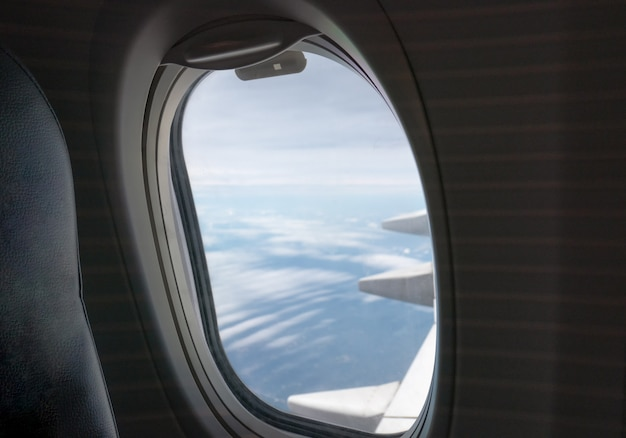 Lado da janela do passageiro com asa de avião voando