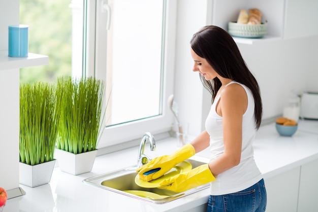 Lado de perfil, verso, foto do lado traseiro de pratos de lavagem de menina alegre positiva use luvas de proteção de borracha amarela esponja ficar perto da janela na cozinha da casa