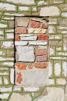 Lado de tijolo de um edifício com musgo crescendo nas fendas com um quadrado vermelho onde parte do tijolo