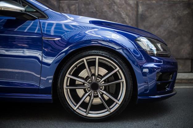 Lado direito dianteiro de um carro sedan azul