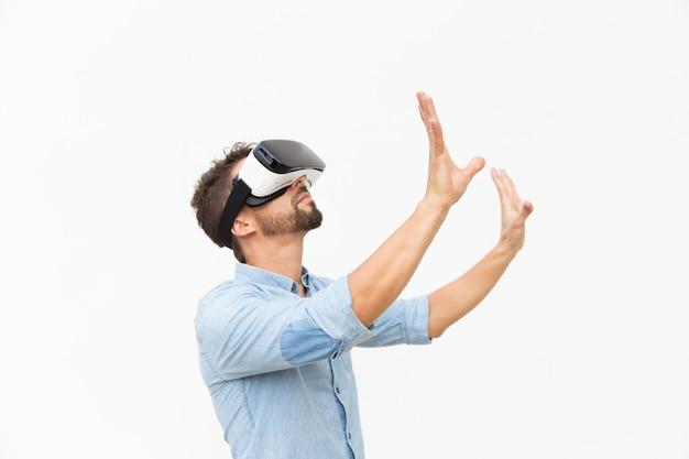 Lado do barbudo usando óculos de realidade virtual, tocando o ar