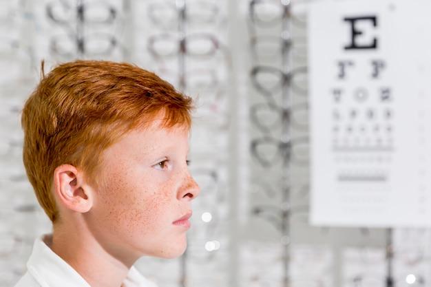 Lado do jovem garoto adorável com sardas no rosto em pé na loja de óptica