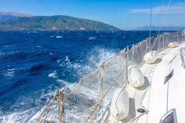 Lado esquerdo de um iate à vela com um guard rail e defensas. dia de sol com vento. mar azul profundo e espuma do mar