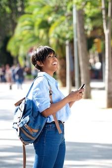 Lado, retrato, jovem, mulher preta, andar, exterior, com, telefone móvel