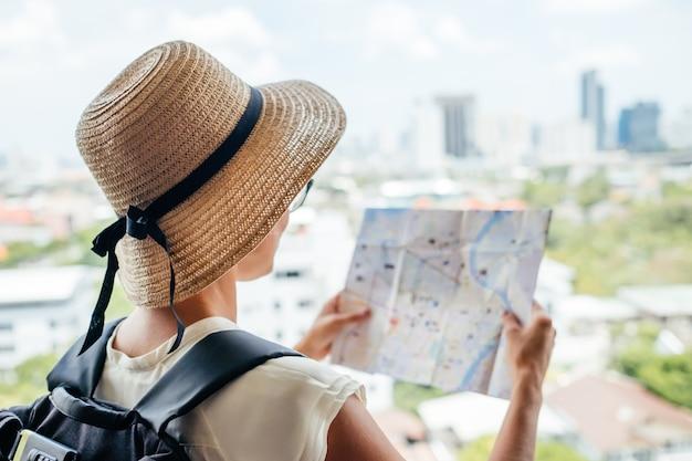 Lado traseiro da garota viajante procurando a direção certa no mapa, viajando pela ásia