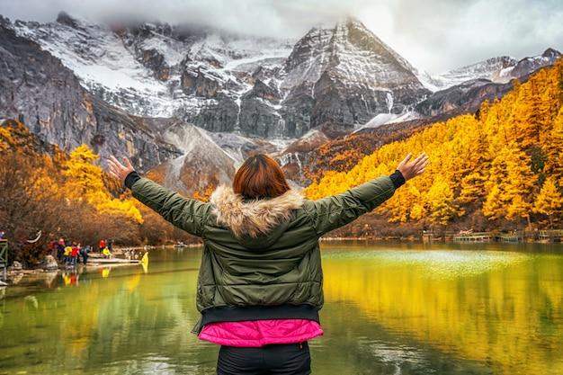 Lado traseiro da mulher asiática viajante olhando e passeando sobre o lago pearl com montanha de neve na temporada de outono na reserva natural yading, china. viagem e turismo, lugar famoso e conceito de marco