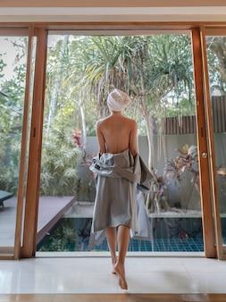 Lado traseiro da mulher tirando o roupão de banho e caminhando para a piscina.