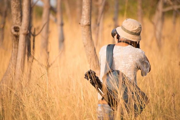 Lado traseiro do homem do fotógrafo no campo de grama cinzento com câmera na mão.