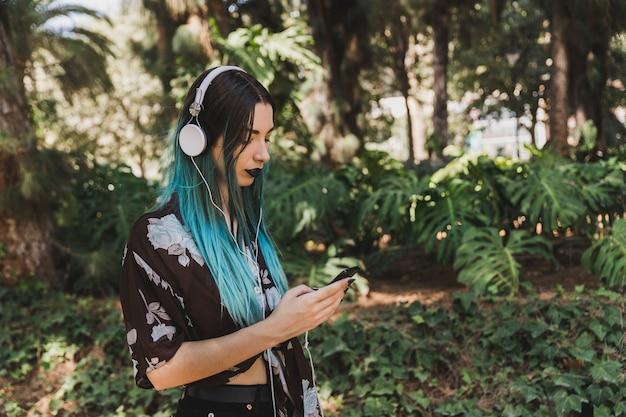Lado, vista, de, mulher, com, cabelo tingido, escutar música, ligado, headphone, usando, esperto, telefone