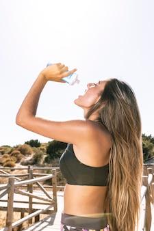 Lado, vista, mulher, hidratar, executando