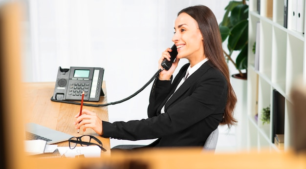 Lado, vista, sorrindo, jovem, mulher, sentando, escritório, falando, telefone