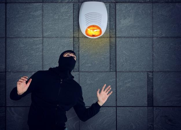 Ladrão com balaclava foi flagrado tentando roubar em um apartamento do sistema de alarme de segurança expressão de medo