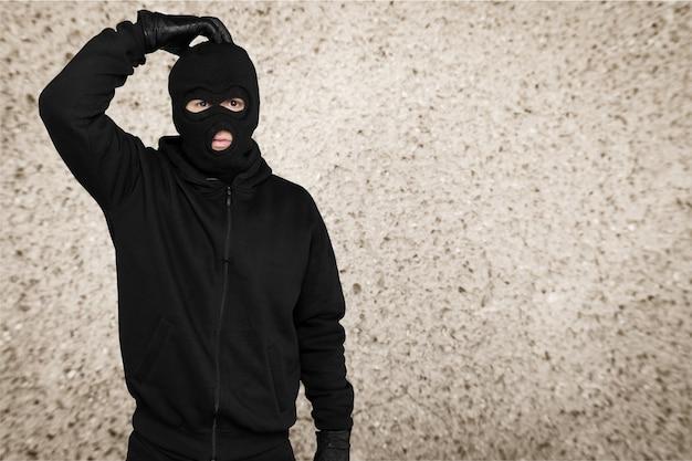 Ladrão com balaclava preta e roupas no fundo