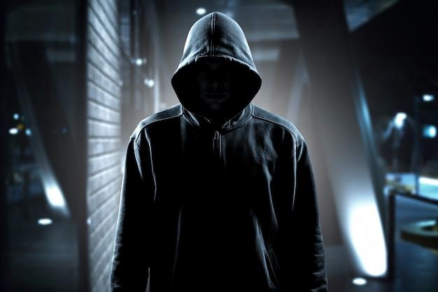Ladrão com roupas pretas no fundo da sala