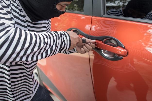 Ladrão e o ladrão de carros em uma máscara abrem a porta do carro e o sequestram.