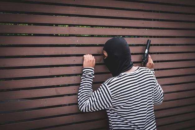 Ladrão escondido atrás da parede