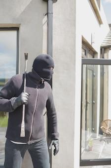 Ladrão escondido atrás de uma parede